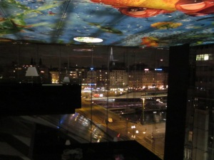 From an inside lounge area at night looking out to the city.